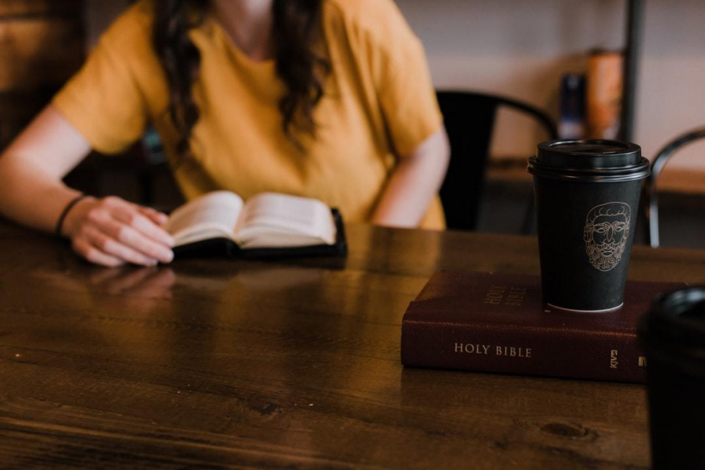 woman reading the bible at a table